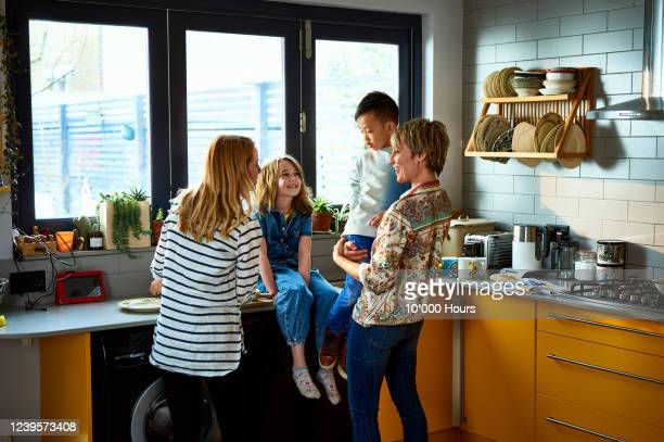 cheerful family with same sex parents in kitchen - lgbtq  and female domestic life fotografías e imágenes de stock