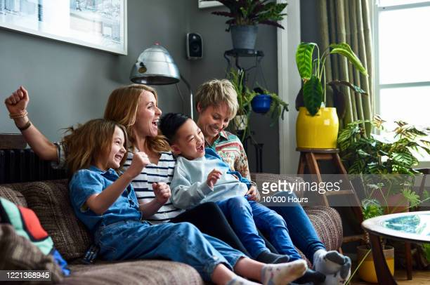 cheerful family with two mums watching tv at home - lgbtq  and female domestic life fotografías e imágenes de stock