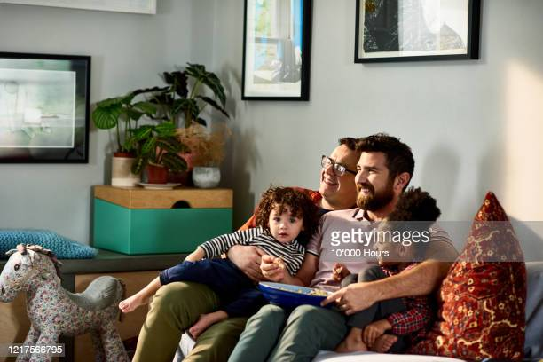 cheerful family with young children on sofa - lgbtq  and female domestic life fotografías e imágenes de stock
