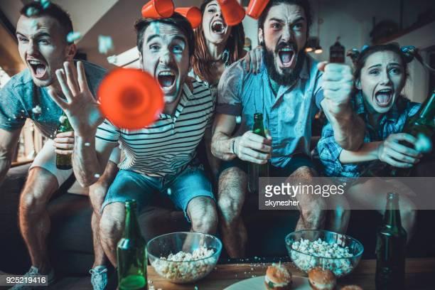 fanáticos alegres gritando mientras celebraba la victoria de su equipo en casa. - hacer un gol fotografías e imágenes de stock