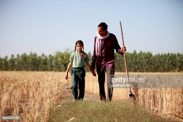 cheerful farmer & his daughter portrait in the wheat field - mid adult stock pictures, royalty-free photos & images