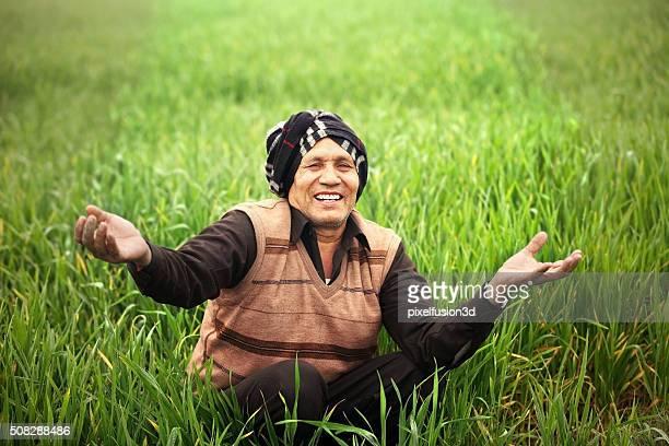 Cheerful Farmer Sitting in the Green field