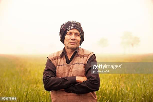 Joyeux agriculteur se tenant debout dans le champ vert