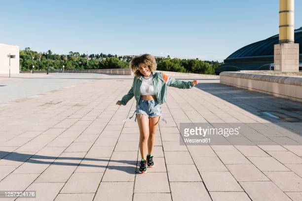cheerful fashionable woman walking on city street during sunny day - hot pants stock-fotos und bilder