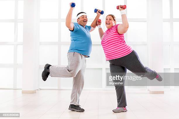 Cheerful fat couple lifting dumbbells and exercising.