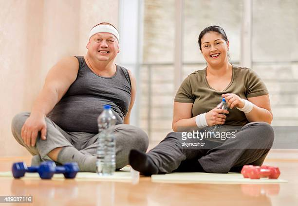 Cheerful fat couple taking a break from exercising.