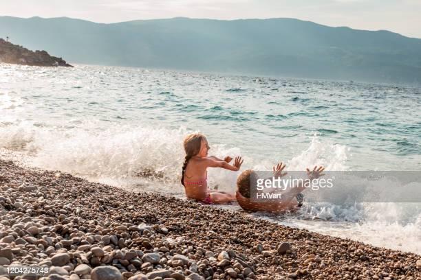 fröhliche vater und tochter im sommerurlaub genießen spritzen im meer und spielen mit wellen - kroatien stock-fotos und bilder