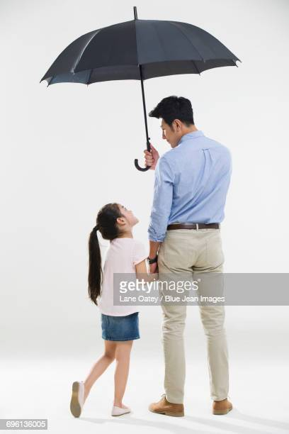 Cheerful father and daughter with an umbrella