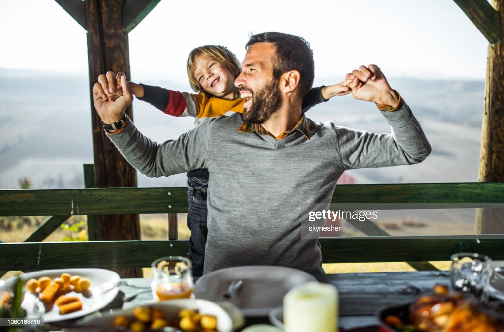 Cheerful father and son having fun during their meal on a terrace. : Stock Photo