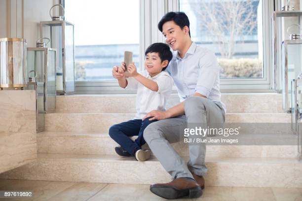 Cheerful father and son taking self portrait in the living room