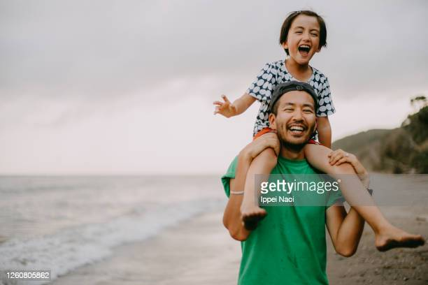 cheerful father carrying his daughter on shoulders on beach - copy space stock pictures, royalty-free photos & images