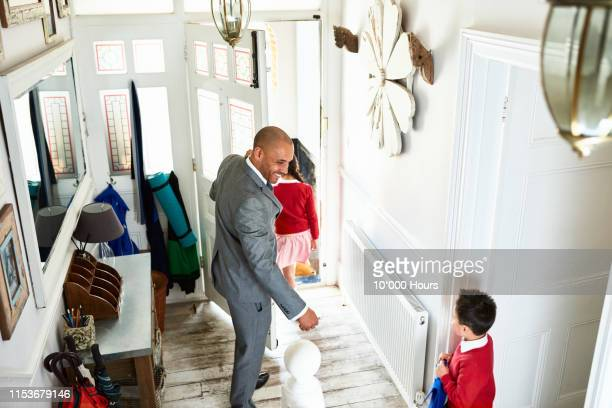 cheerful father in suit taking children to school - leaving stock pictures, royalty-free photos & images