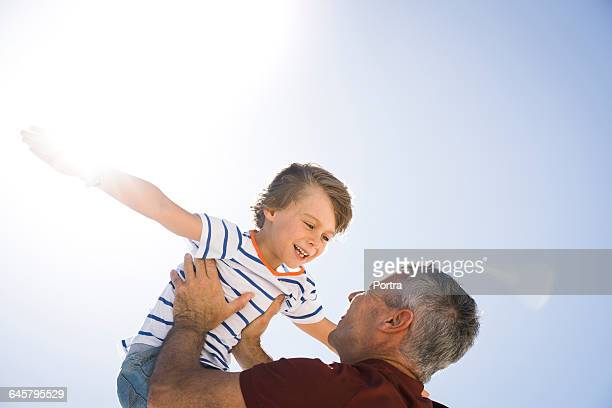 Cheerful father lifting son against sky