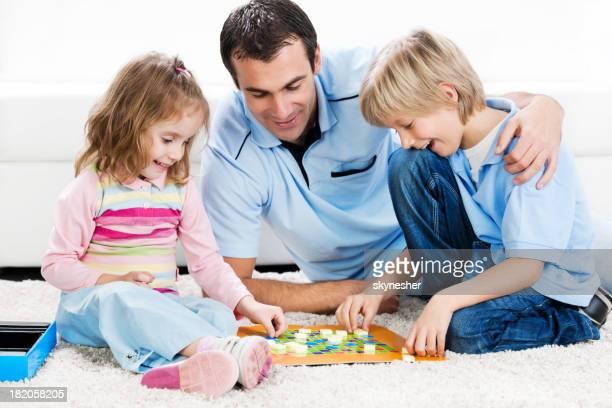 Fröhlich Vater spielen Brettspiel mit seinen Kindern.
