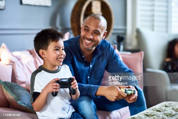 cheerful father playing games console with son - playing stock pictures, royalty-free photos & images