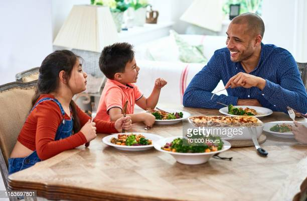cheerful father smiling and talking with family at meal time - filipino family dinner stock pictures, royalty-free photos & images
