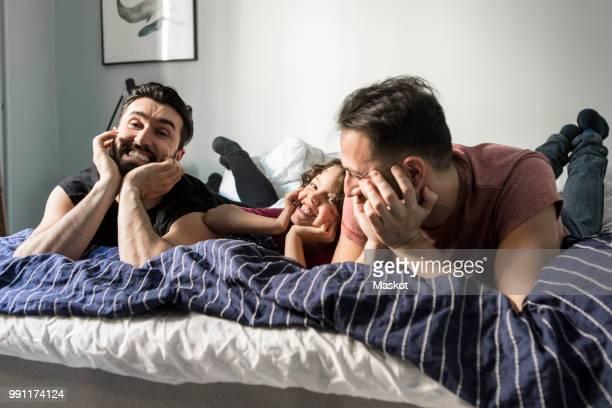 cheerful fathers and daughter lying with head in hands on bed at home - op de buik liggen stockfoto's en -beelden