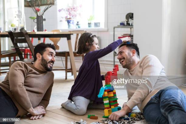 cheerful fathers and daughter playing with toy blocks at home - gay rights stock pictures, royalty-free photos & images