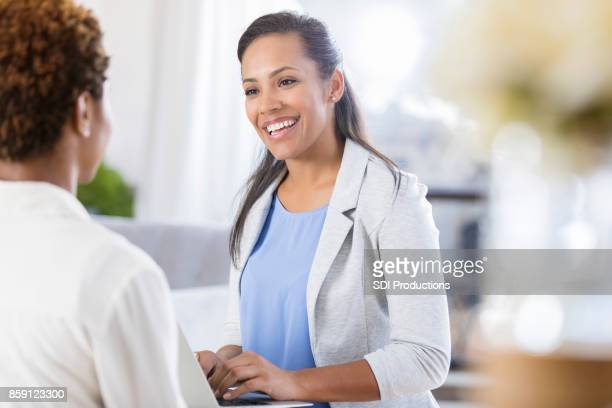 cheerful female accountant uses laptop while meeting with client - secretary stock photos and pictures