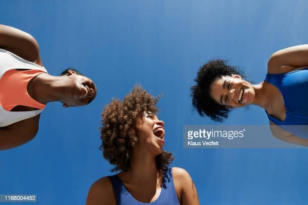 cheerful female athletes in sportswear against blue sky - guardare verso il basso foto e immagini stock