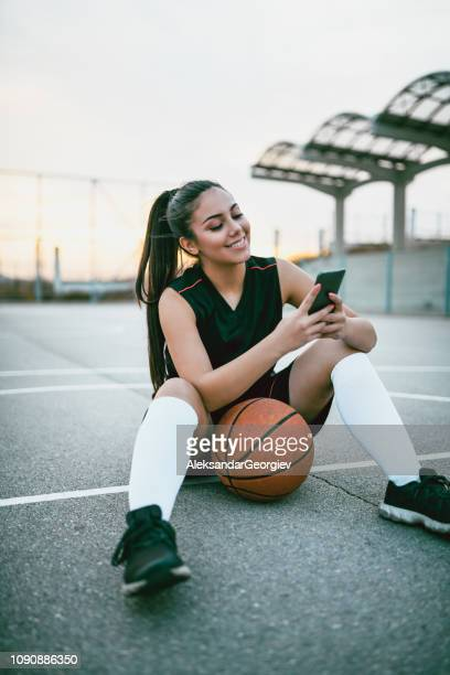 Cheerful Female Basketball Player Typing On Mobile Phone