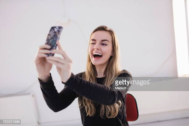 Cheerful female blogger winking while taking selfie through smart phone in office