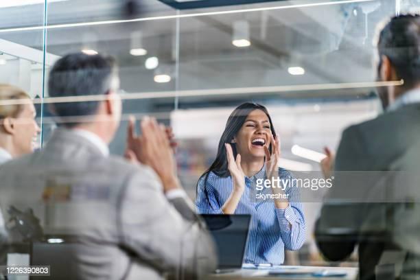 fröhliche kandidatin feiert einen job auf einem interview im büro. - kandidat stock-fotos und bilder
