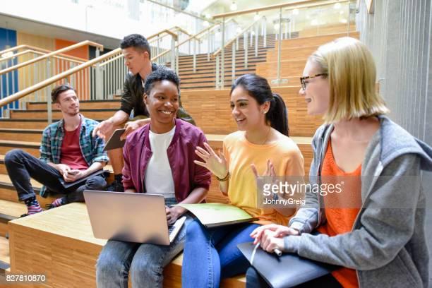 Fröhliche weibliche College-Freunde sitzen auf Stufen mit Laptop und Ordner