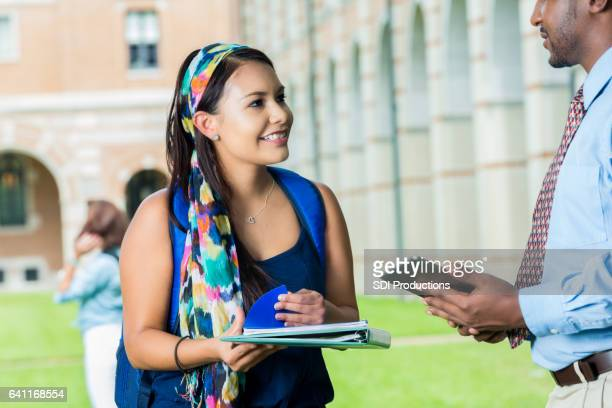 Cheerful female college student talks with professor