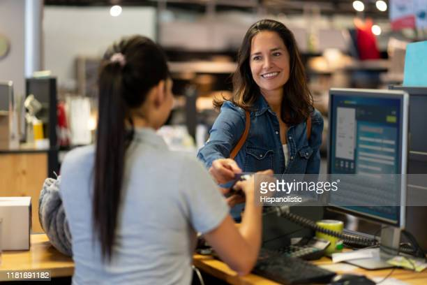 cheerful female customer making a contactless payment with credit card at a furniture store smiling - cash register stock pictures, royalty-free photos & images