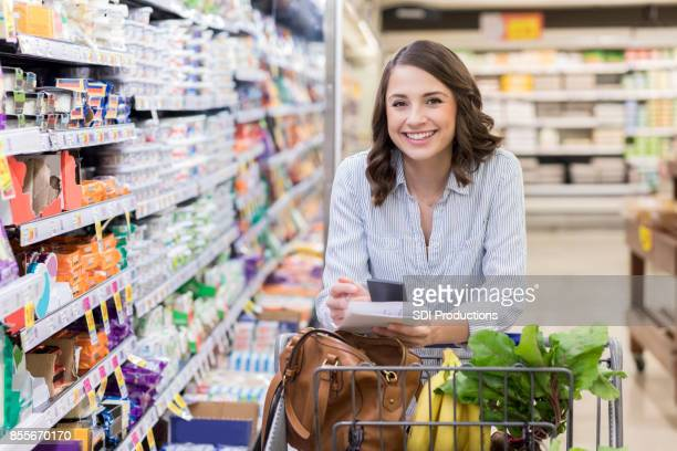 Cheerful female customer shops in a grocery store