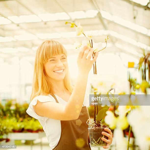 Cheerful Female Florist Nursery Flowers.