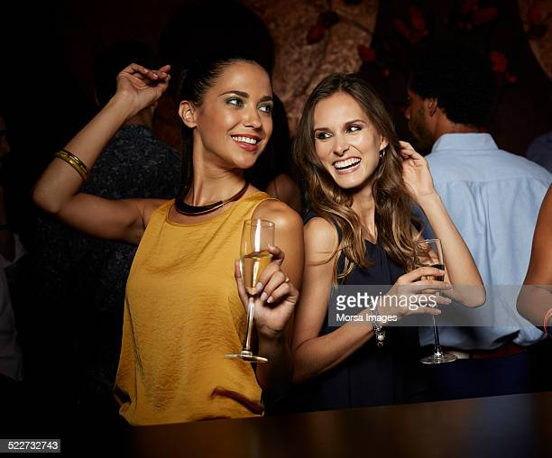 cheerful female friends dancing in nightclub - dancing stockfoto's en -beelden