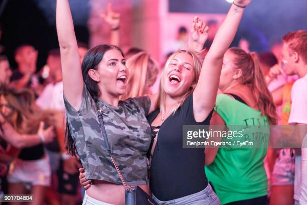 Cheerful Female Friends Enjoying During Music Festival At Night
