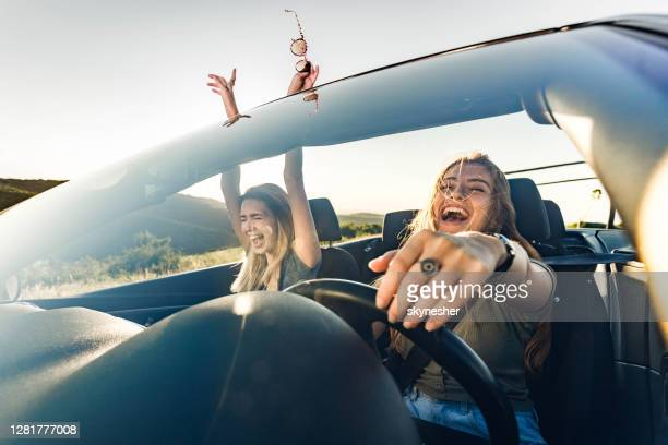 cheerful female friends going on a trip in convertible car. - singing stock pictures, royalty-free photos & images