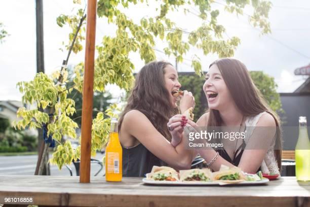Cheerful female friends having food sidewalk cafe