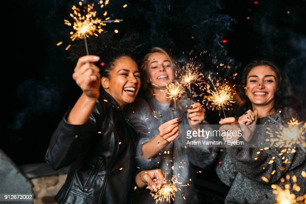 cheerful female friends holding illuminated sparklers - sparkler stock pictures, royalty-free photos & images