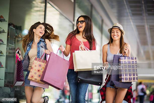 Cheerful female friends running with shopping bags outdoors.