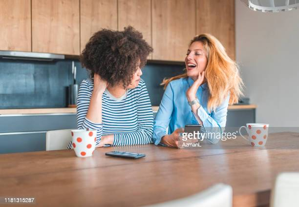 cheerful female friends sitting at dining table - female friendship stock pictures, royalty-free photos & images
