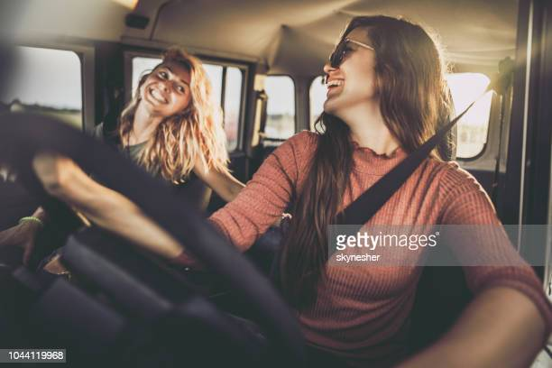 cheerful female friends talking during a road trip in a car. - driver stock pictures, royalty-free photos & images