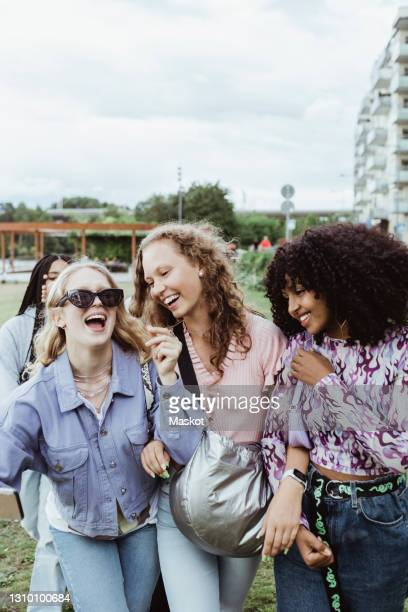 cheerful female friends walking in park - sweden stock pictures, royalty-free photos & images