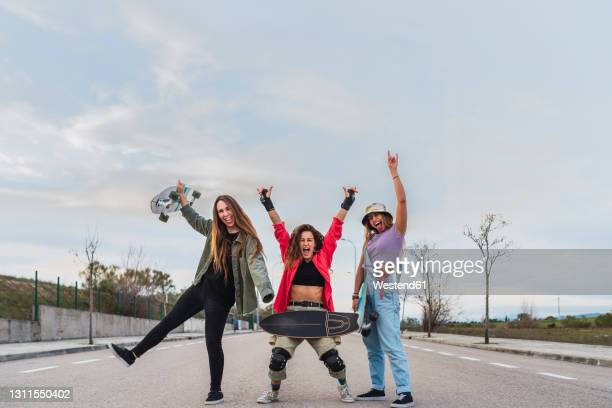 cheerful female friends with skateboard gesturing on road - fingerless gloves stock pictures, royalty-free photos & images