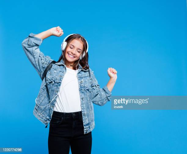 cheerful female high school student listening to music - teenager stock pictures, royalty-free photos & images