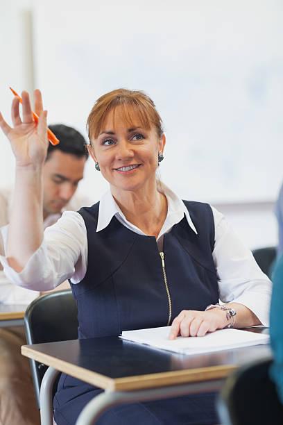 Cheerful female mature student raising her hand