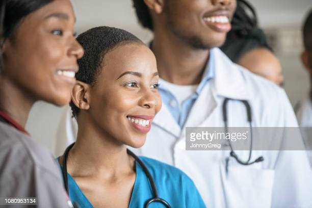 cheerful female nurse with colleagues looking away and smiling - junior doctor stock pictures, royalty-free photos & images
