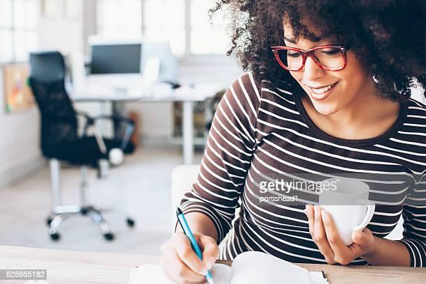 Alegre mujer trabajador de oficina sentado sobre un escritorio