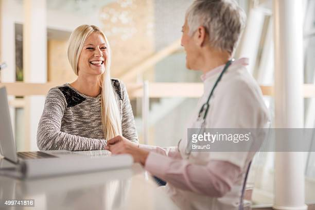 Cheerful female patient talking to a doctor at doctor's office.
