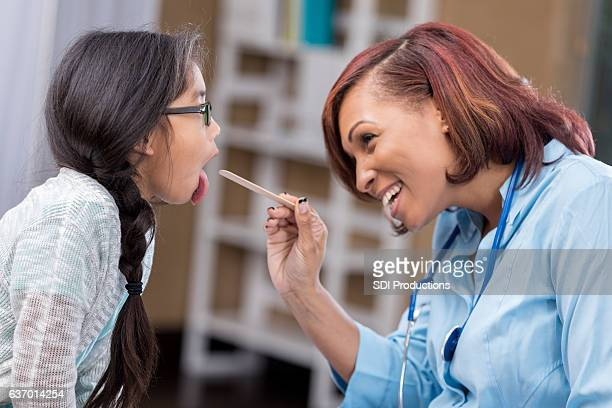 Cheerful female pediatrician checks young patient's throat