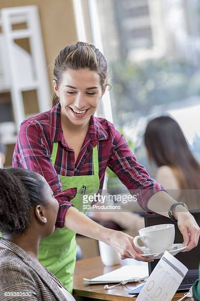 Cheerful female server serves coffee to business woman