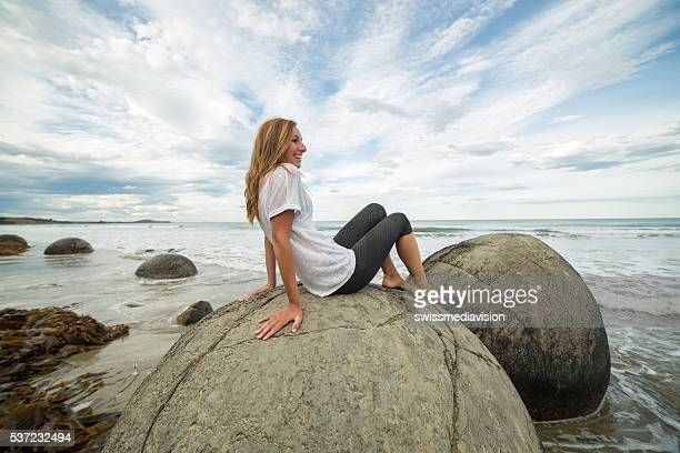 Cheerful female sits on boulder at sea,looks at view